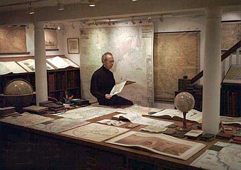 david rumsey amid items of his map atlas and globe collection